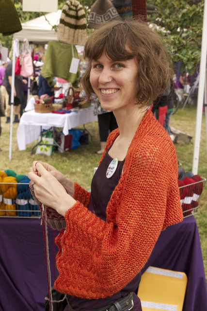 Andrea knitting at her booth
