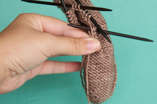Throw a loop of yarn over the needle
