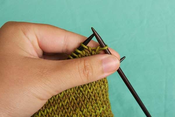 Move the stitch from the left needle to the right needle