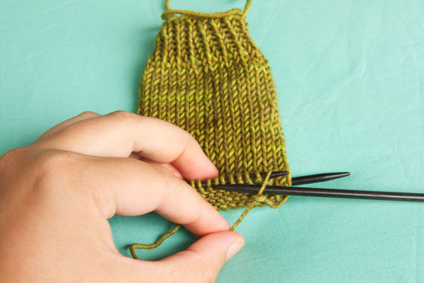 Insert the right needle into the first stitch on the left needle as if to purl