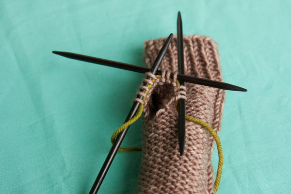 After the stitches are on the needle you can remove the waste yarn.