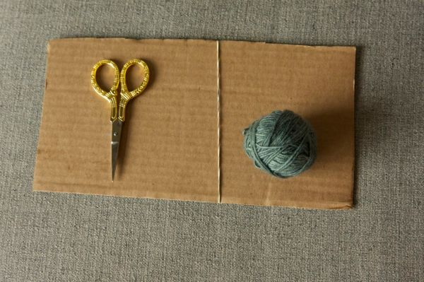 Cardboard (twice the length of your desired fringe), an elastic band, scissors, and yarn