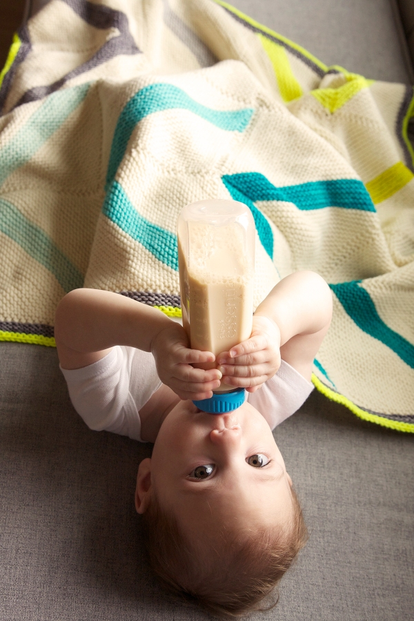 Baby drinking from a bottle under fly away blanket