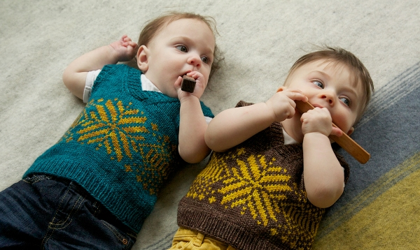 Max and Bodhi are about 6 months old lying on a wool blanket. They are wearing matching colourwork vests and chewing on wooden blocks.