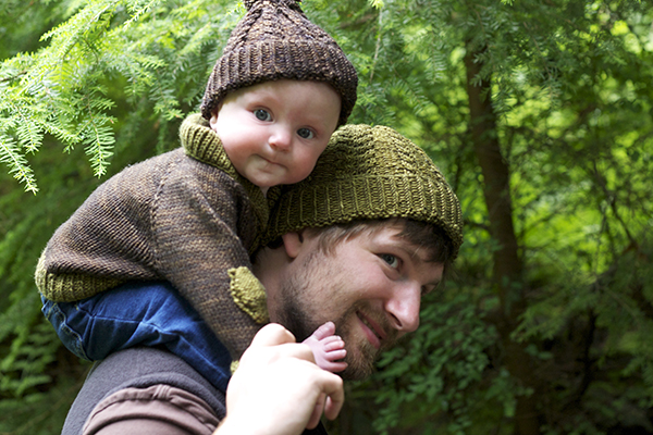 a small Hunter is on Gary's shoulders, decked out in a knit sweater and hat. Gary is wearing a coordinated hat too as they tromp through the woods.