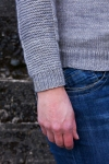 cuff of a grey sweater with garter stitch panel
