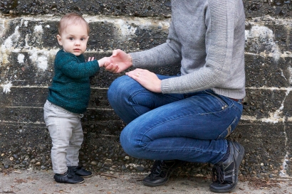 baby in teal sweater holding adult's hand