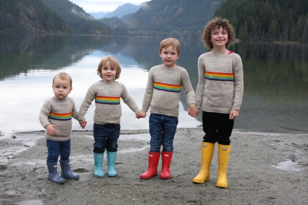 Four children in sweaters with rainbow stripes on the shore of a calm lake.