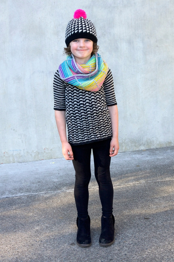 A kid wearing colourwork hat, striped cowl and striped sweater.
