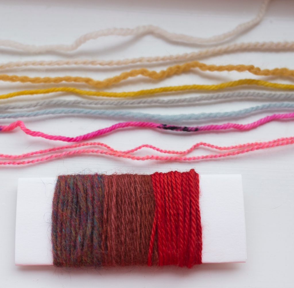 A card wrapped in yarns with different textures and constructions, and strands of different yarns laid alongside.