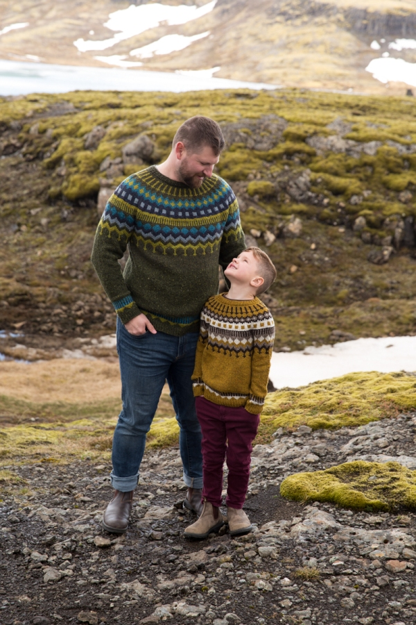 Gary and Jones in matching hand knit colourwork yoke sweaters. They stand against a backdrop of snow and mossy rocks.
