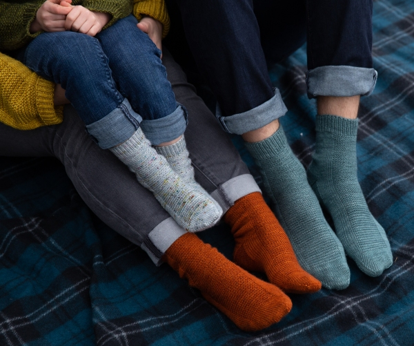 grey, orange, and teal socks with garter panels on child and adult sized feet