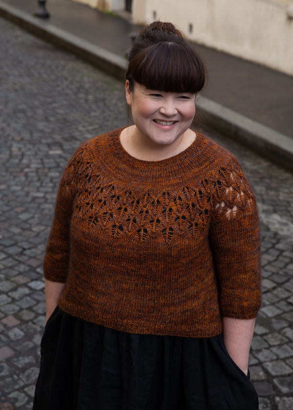 Aimee is standing in a cobblestone street wearing her orange lace yoke sweater. Her hands are in her pockets and she is smiling.