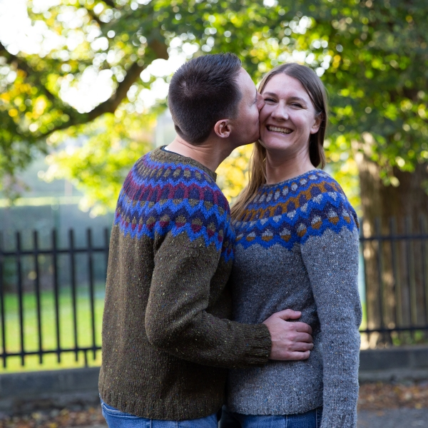 2 adults in matching sweaters. The man is kissing the woman on the cheek.