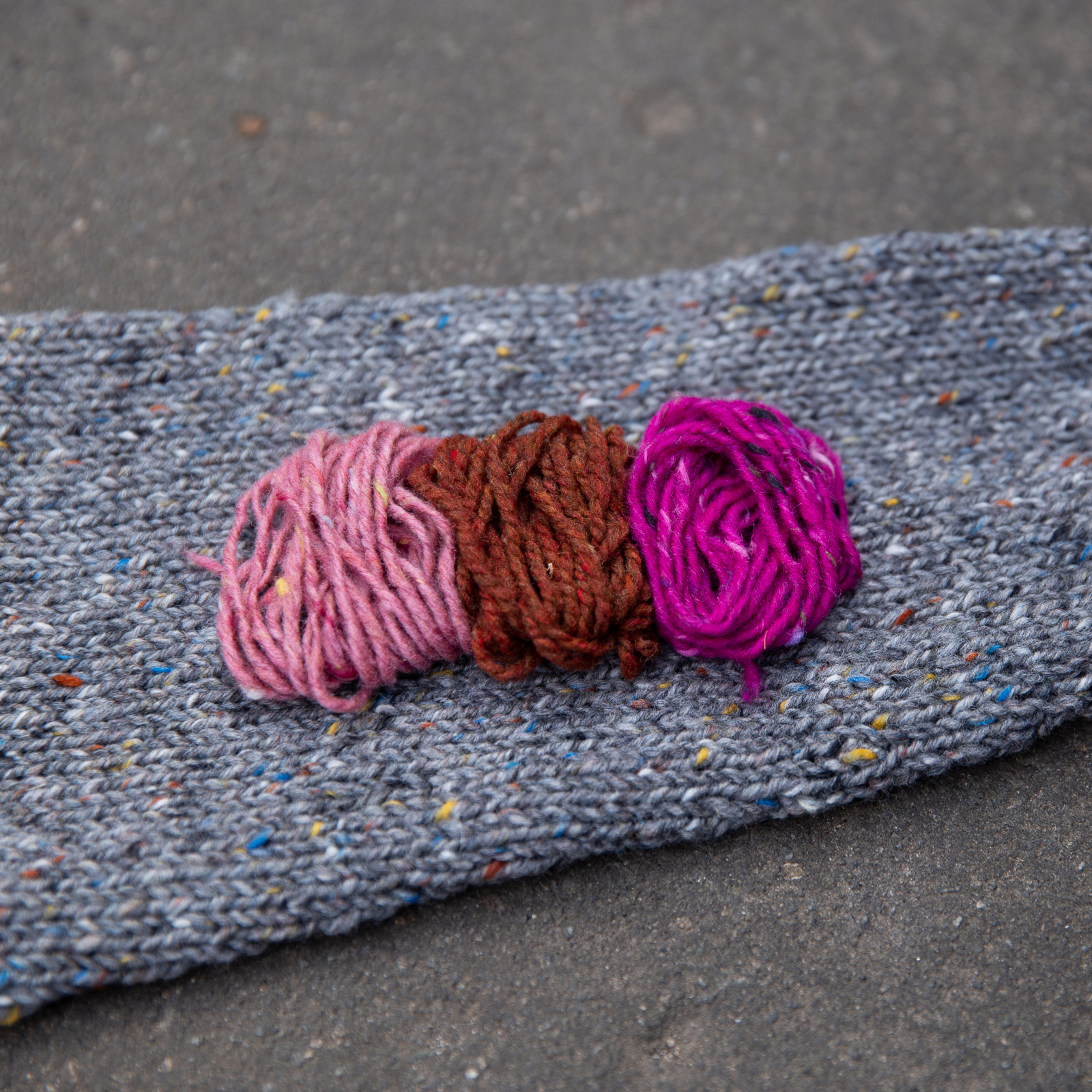 yarn palette of light pink, rust, and fucsia