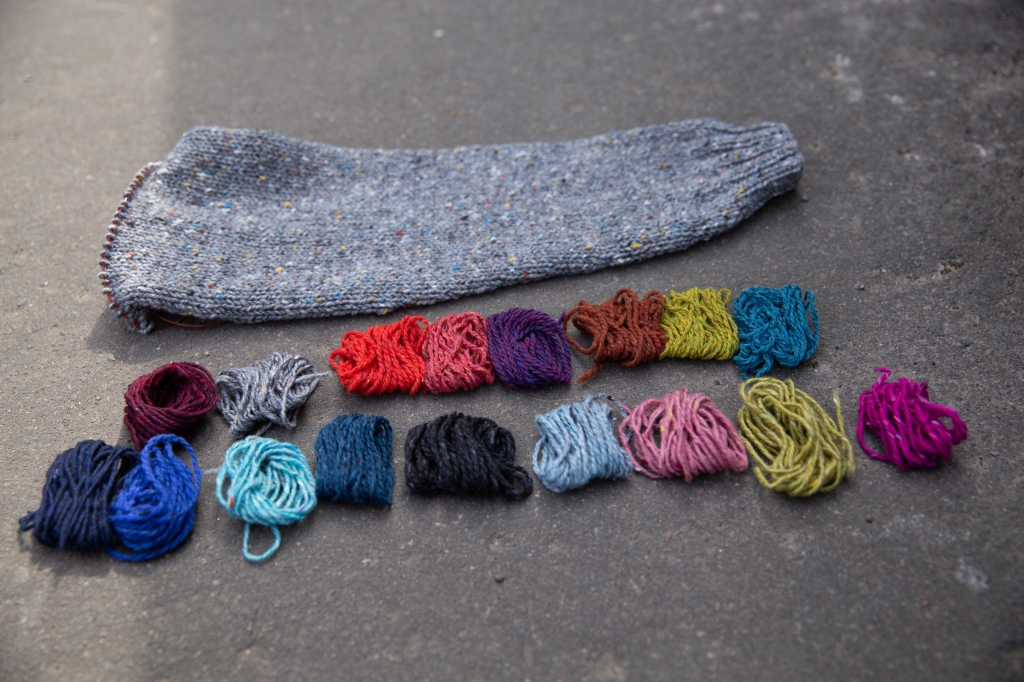A knit sleeve next to bits of yarn in various colour combinations