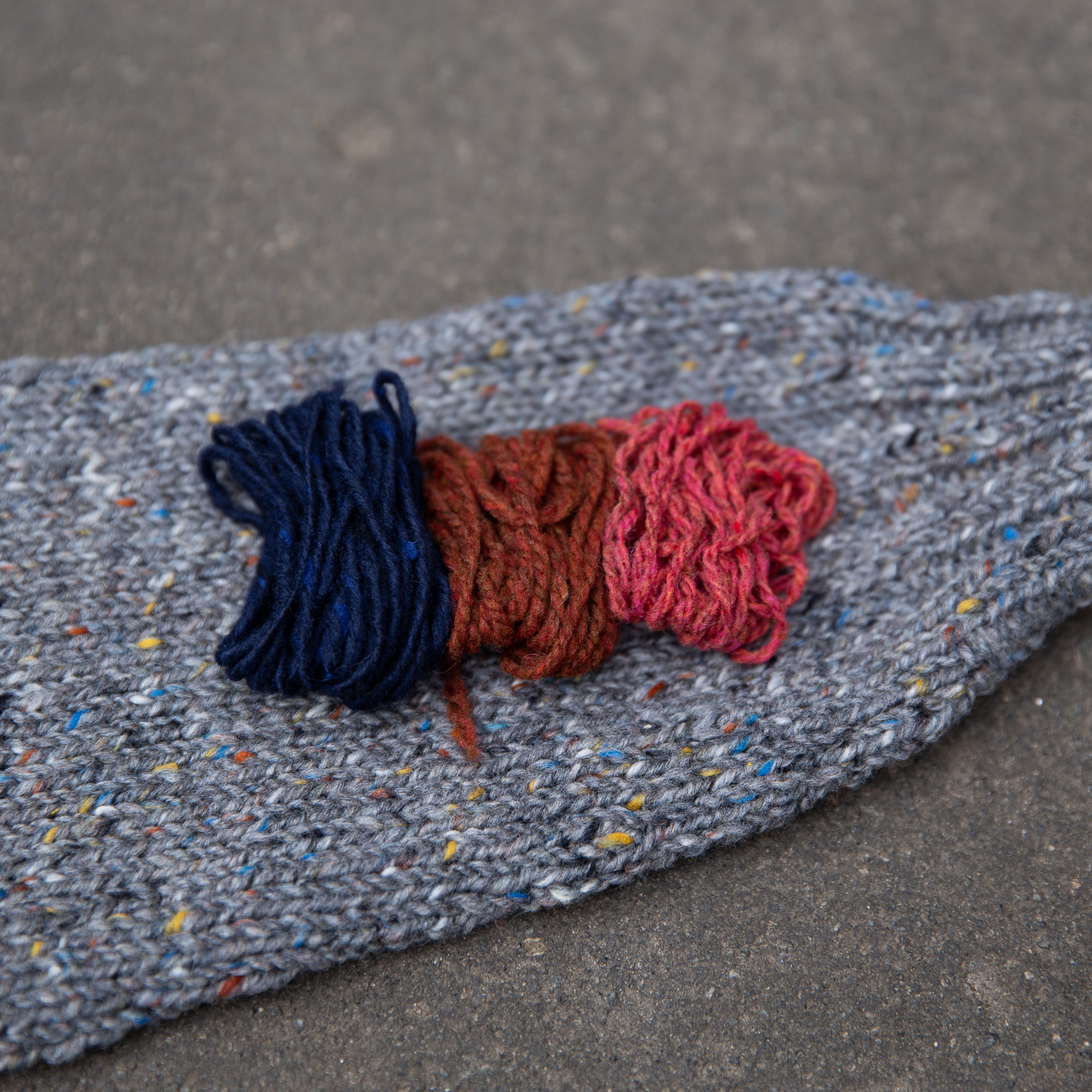 yarn palette of navy blue, rust, salmon