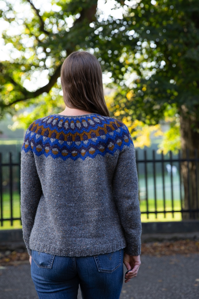 An adult woman wearing a handknit sweater with a colourwork yoke.