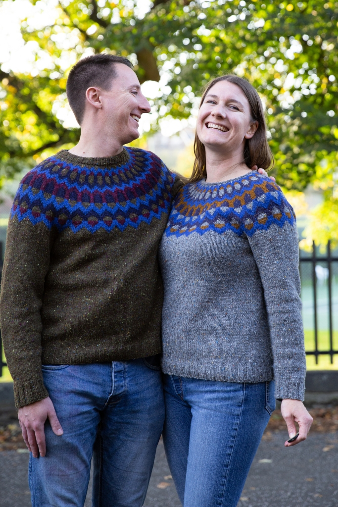 An adult couple wearing matching knit sweaters and laughing.