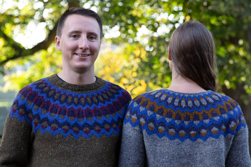 2 adults wearing matching handknit sweaters