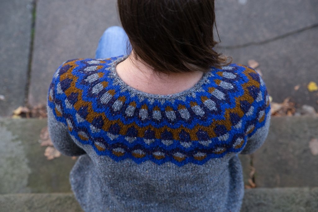 Woman on a step wearing a handknit sweater with a colourwork yoke.
