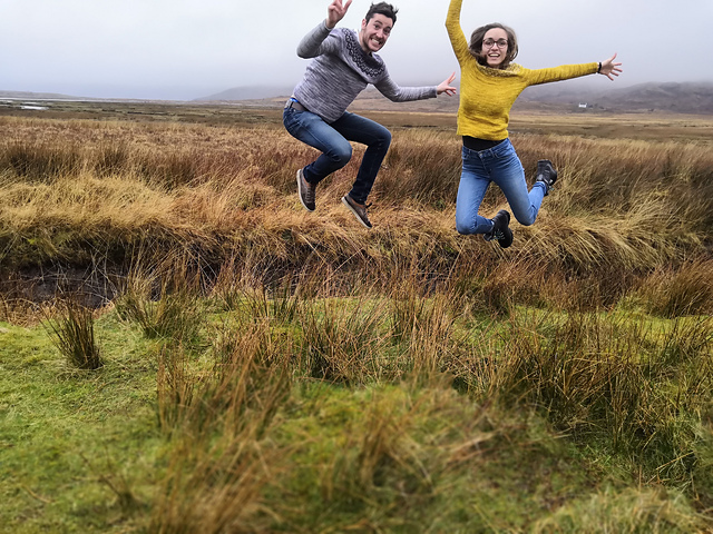 Woman and man in yellow and grey sweaters leaping off the ground.