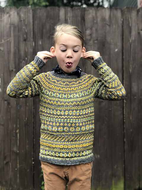 Kid wearing grey and yellow Cartography colourwork sweater