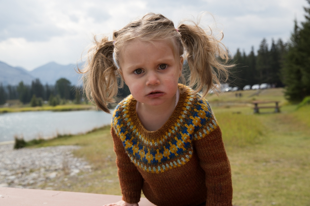 A toddler with pigtails and a frowny face wearing a colourwork yoke sweater with lake and mountains in the background.