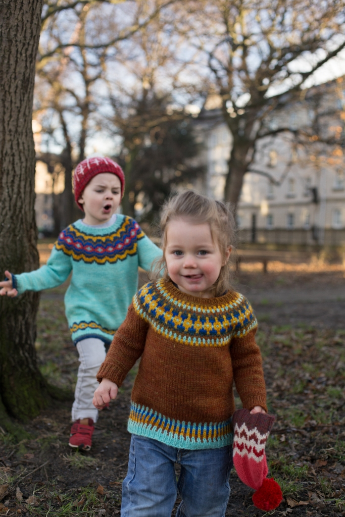 Two toddlers playing in a park, wearing colourful yoke sweaters.