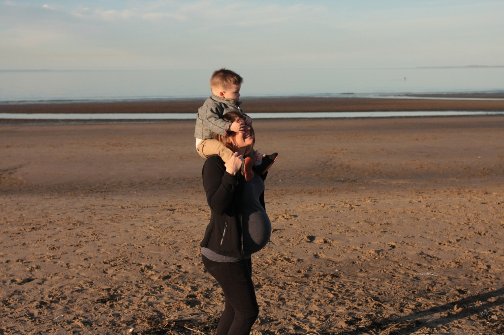 Pregnant woman at the beach, carrying a toddler on her shoulders.