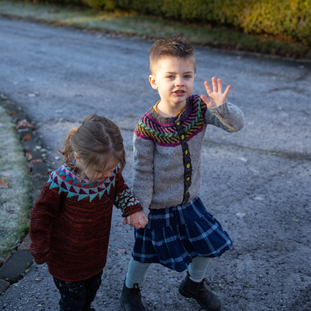 Children in colourwork yoke jumpers holding hands on a frosty driveway.