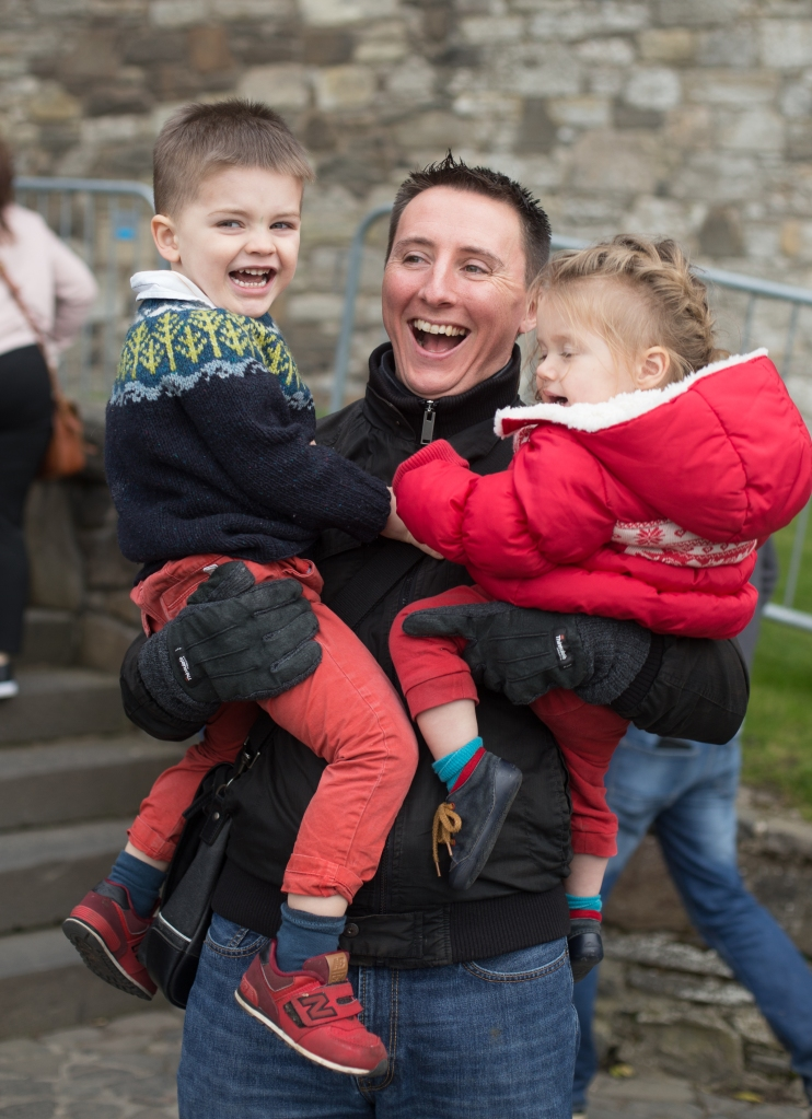 A smiling man holds two toddlers, one in each arm.