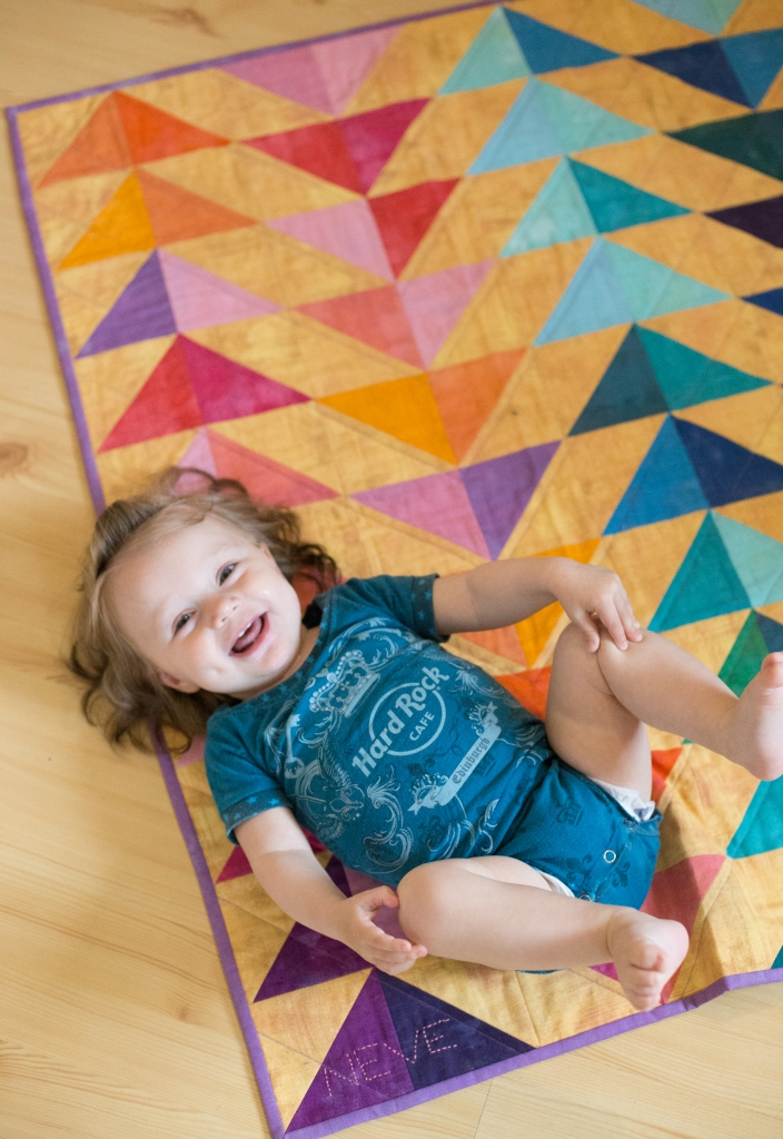 One year old baby in a teal onesie, lying on a rainbow quilt.
