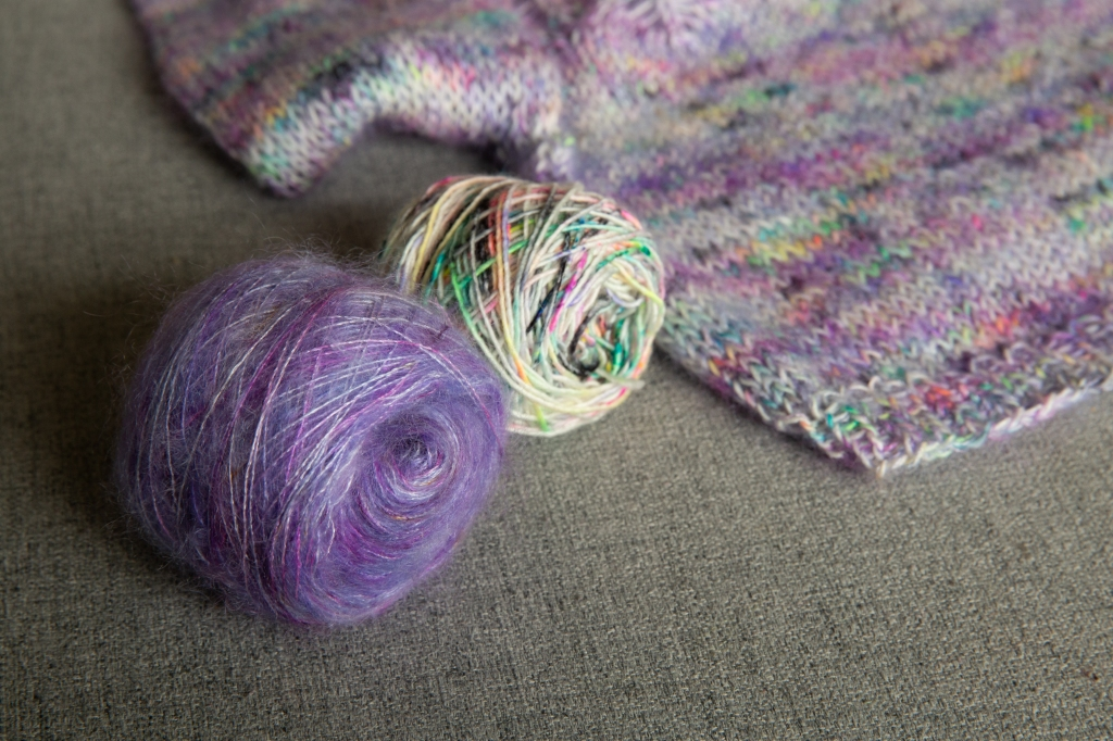 2 balls of yarn, one purple mohair, the other white with speckles next to a sweater laid flat.