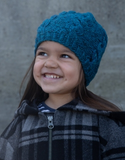 smiling child in a cabled hat