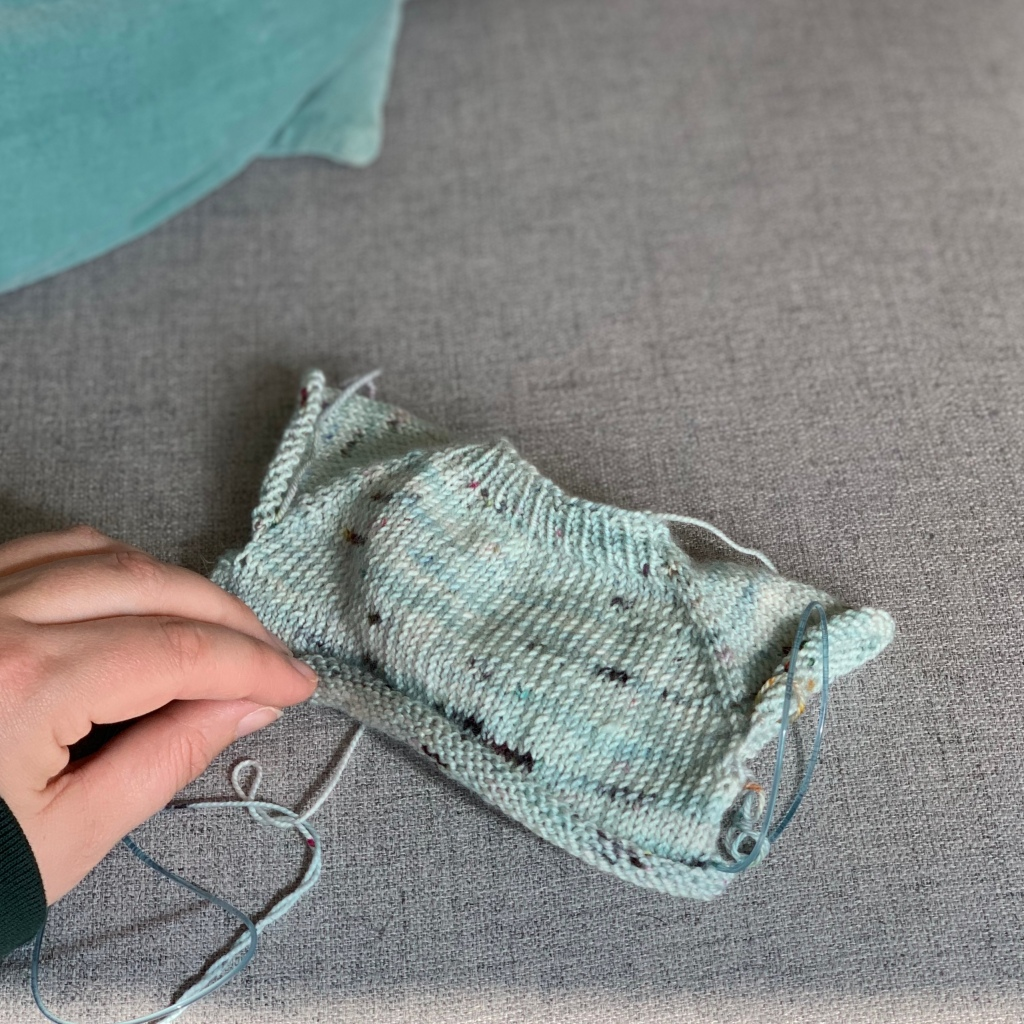 A tiny blue sweater in progress against a grey background.