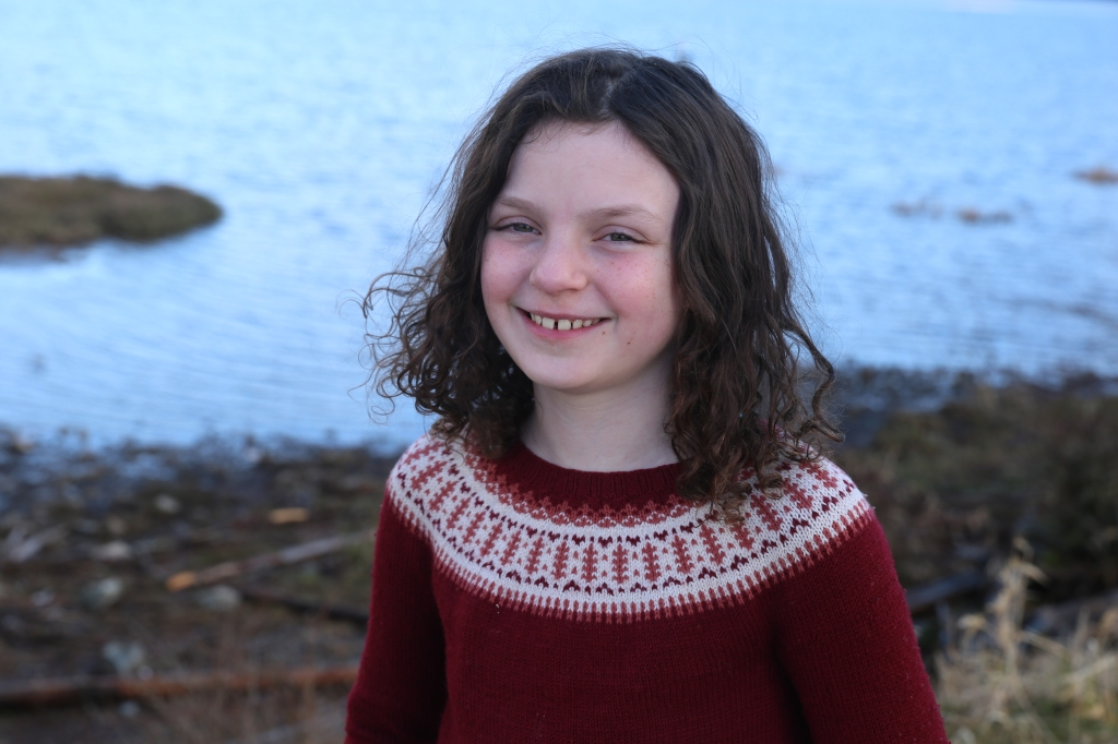Hunter smiling in her hand knit colourwork yoke sweater. Backdrop is beach and water.