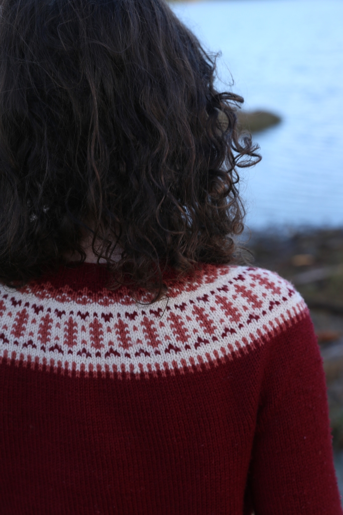 Close up of colourwork yoke. Hunter faces the water and her curly hair is loose.