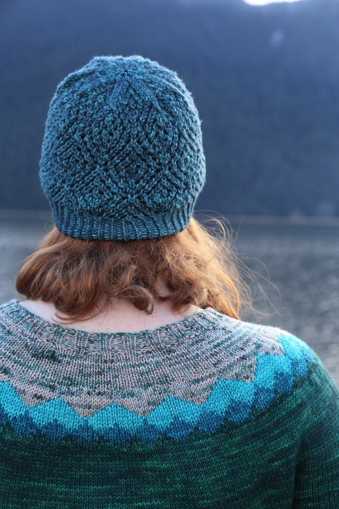 Michelle turned away facing the mountains, with a handknit lace hat and a handknit colourwork yoke sweater.