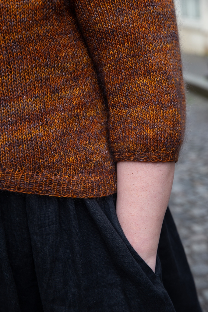 A detail of the high low hem of the Love Note sweater. Aimee has her hand in her pocket and the curve of the hem is visible.