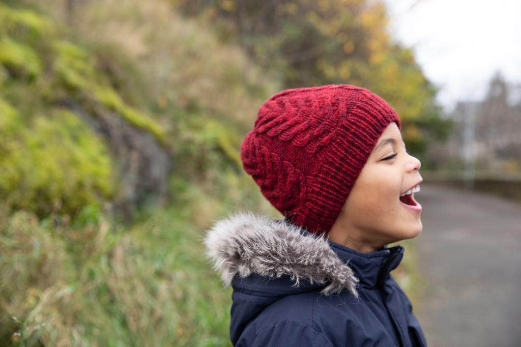 laughing child in red cabled hat