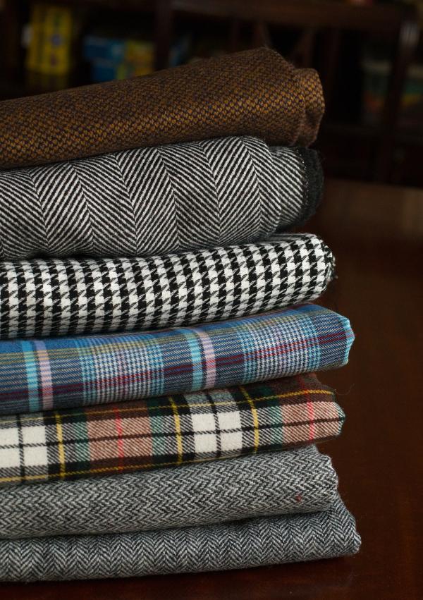 stack of woollen tweed fabrics in earthy tones