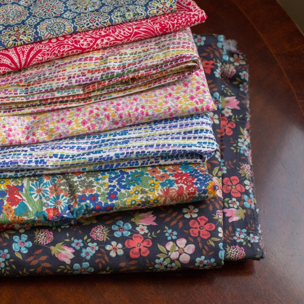 a stack of floral and graphic printed fabrics