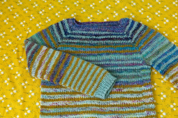 A striped raglan sweater in purple, pale teal, gold and green laid flat on a yellow quilt