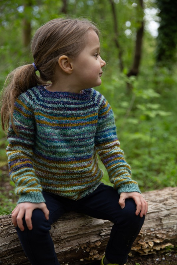 Little kid in a striped raglan sweater in purple, pale teal, gold and green, sitting on a log.