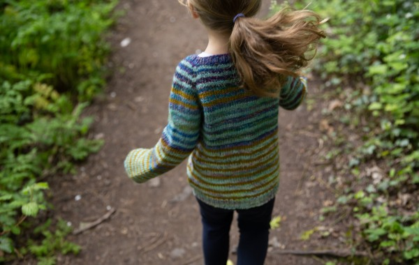 A child, ponytail swinging, runs along a forest path wearing a striped sweater.
