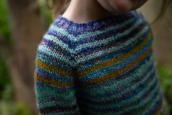 The yoke of a striped sweater in purple, pale blue, and golden yellow