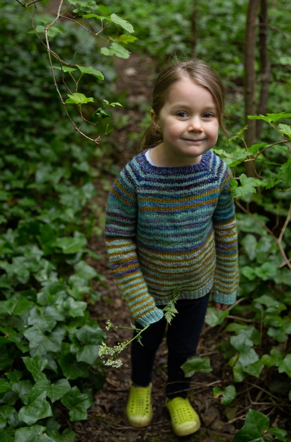 Child smiles up at the camera, framed by green underbrush wearing a striped sweater.