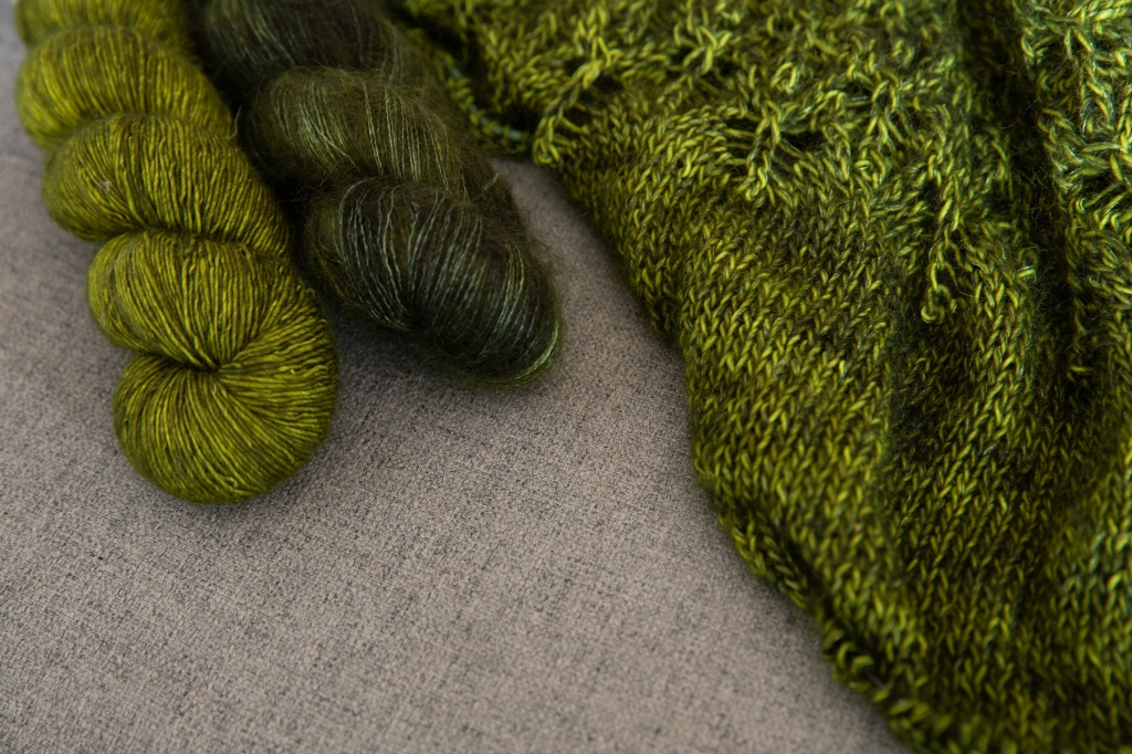 skeins of green yarn and a partially knit item