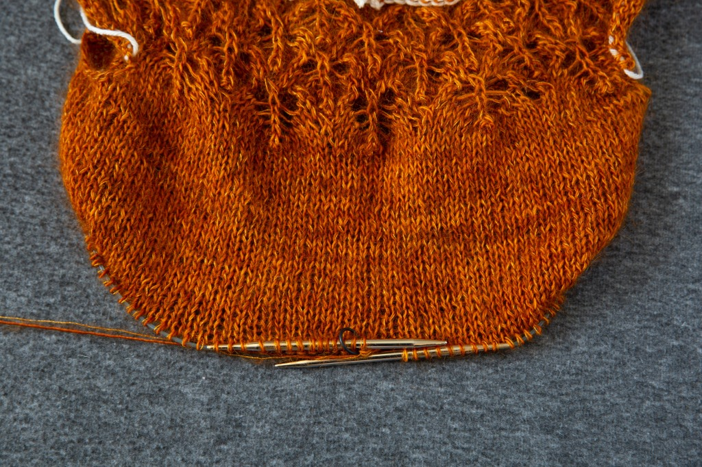 An orange sweater with the needles still in the body of the sweater. A black marker notes the beginning of the round at the centre back of the sweater.